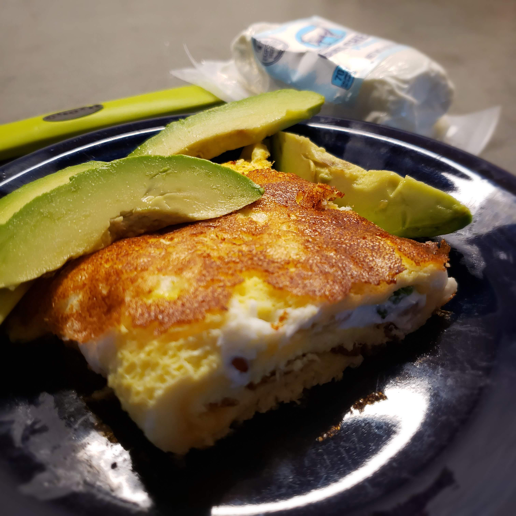 Plated omelette with avocado slices