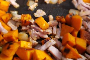 Sweet potato cubes, chopped onions, and thinly sliced pork sauteing