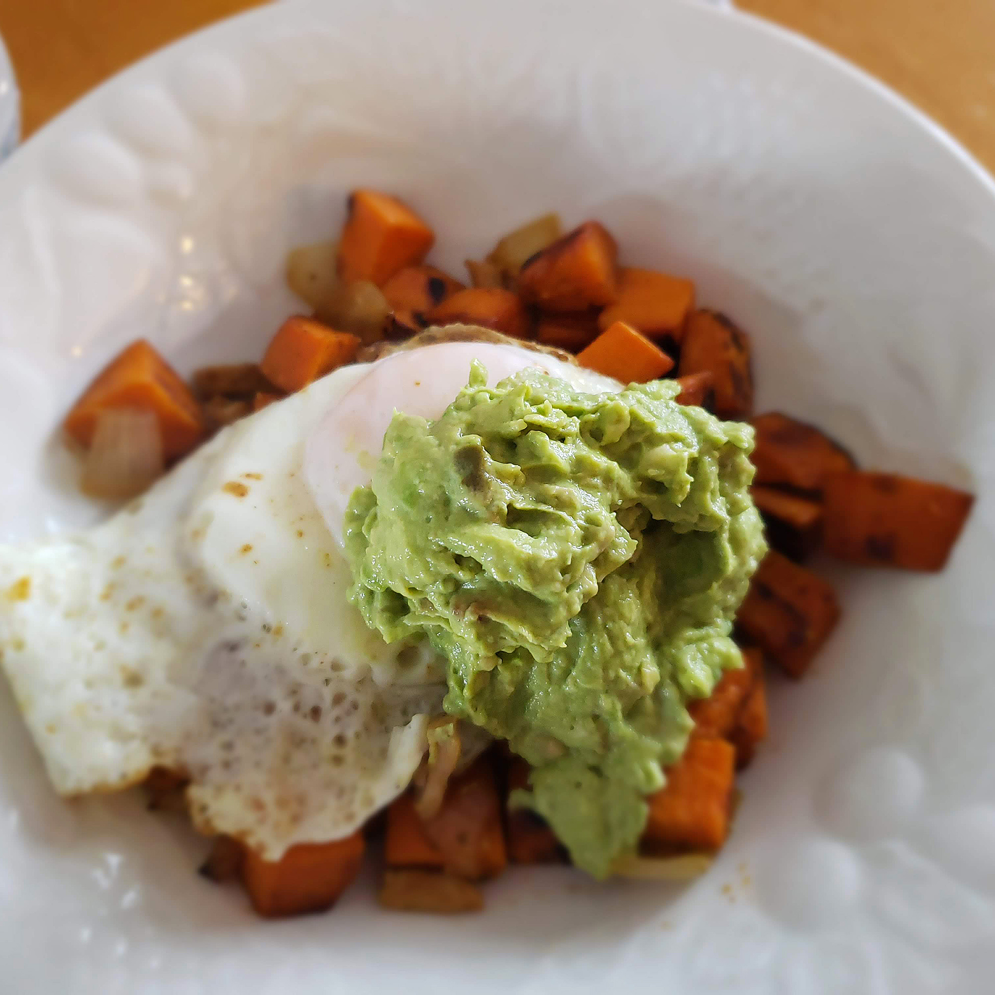 Sweet potato hash with fried egg and avocado aioli on a white plate