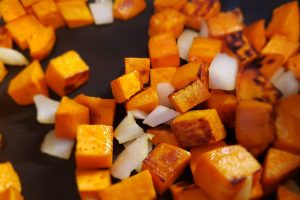 Sweet potato cubes and onions sauteing in skillet