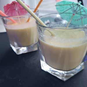 Banana Mango Smoothies in glasses with straws and umbrellas