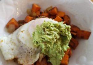 Sweet potato hash with fried egg and avocado aioli on a white plate