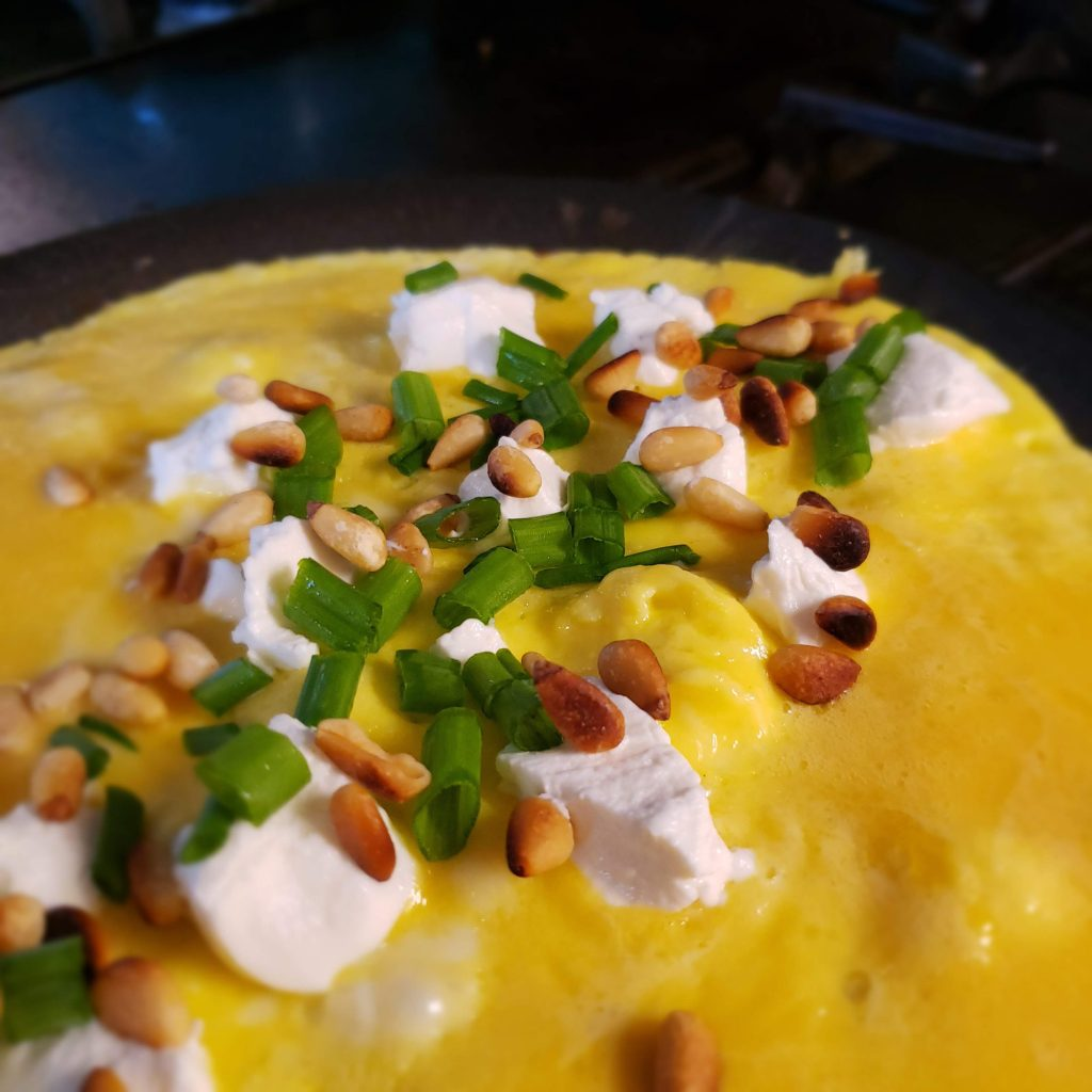 Omelette with feta cheese, green onions, and pine nuts in the skillet